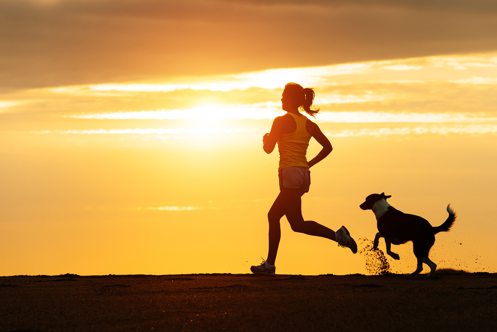 Woman running with her dog in summer.
